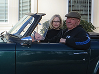 A photo of Maureen and David Wadiak sitting in their convertible.