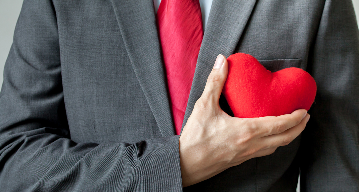A person in a suit holding a plush heart.